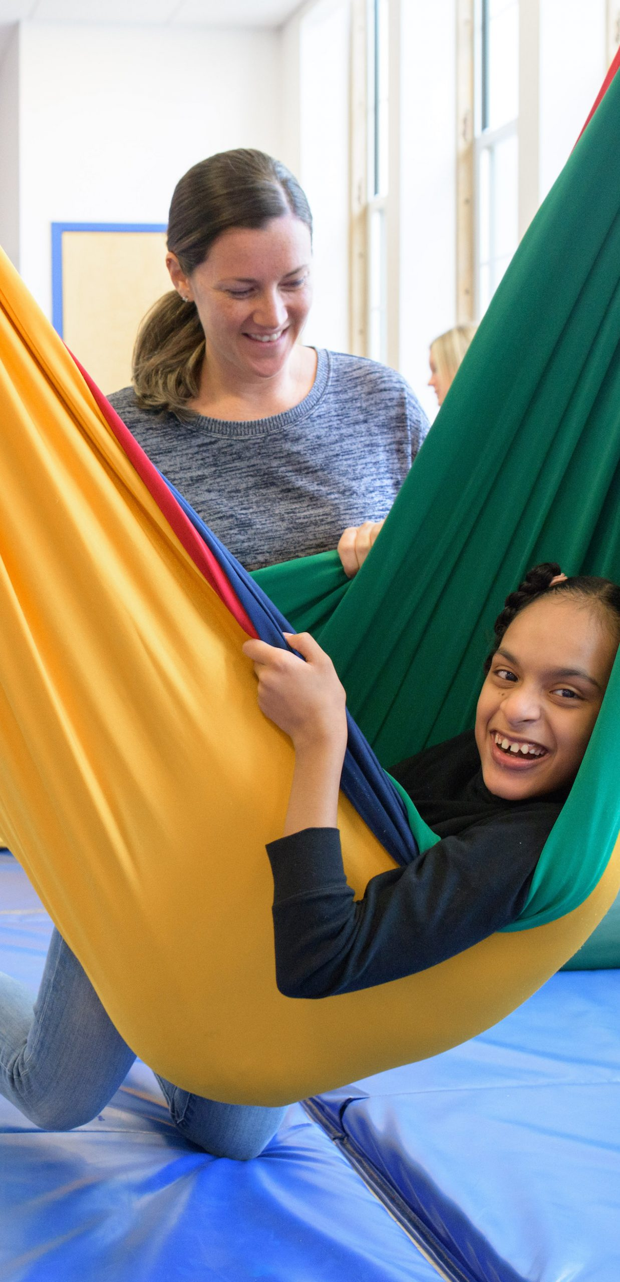 Student in hammock with therapist watching